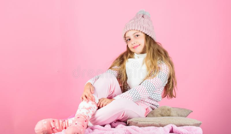 Warm accessories that will keep you cozy this winter. Kid girl wear knitted warm hat relaxing pink background. Winter. Fashion warm clothes concept stock photography
