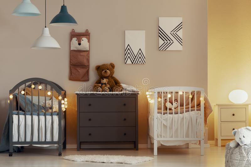 Warm baby bedroom interior with white and grey cribs, commode and small nightstand table with lamp stock images