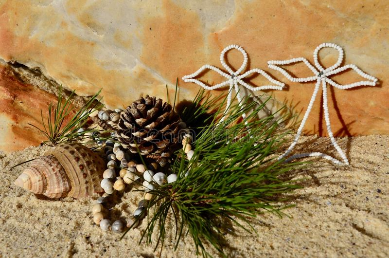 Warm Beach Christmas pine cone white beaded angels beach sand and shell Christmas in July stock images
