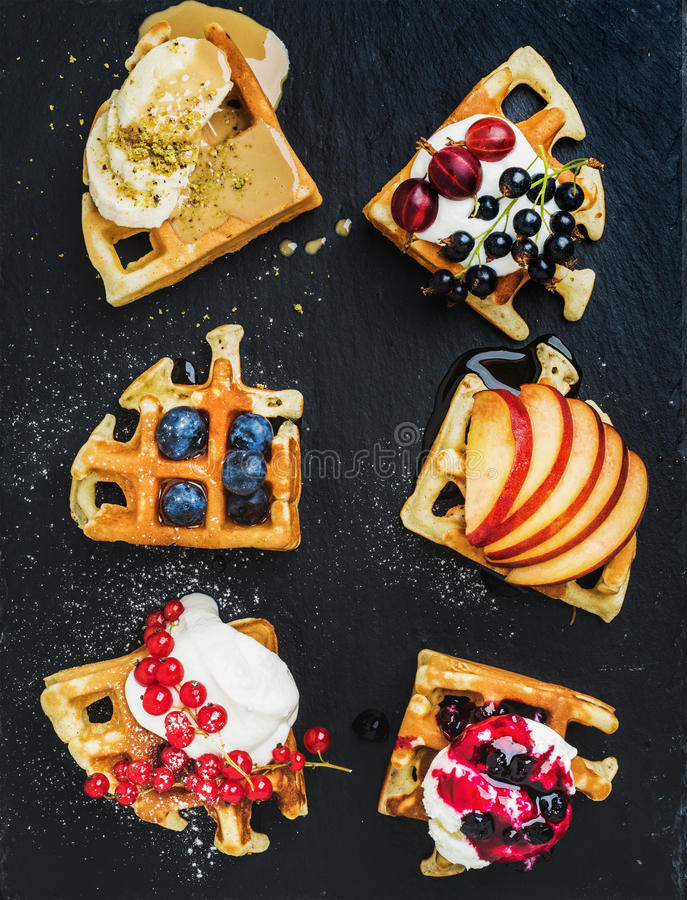 Warm belgian homemade waffles with fresh garden berries, fruit and ice cream on dark slate stone background royalty free stock photography