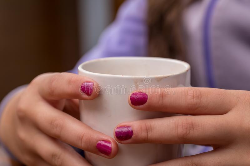 Warm beverage. A girl holding a warm beverage stock images