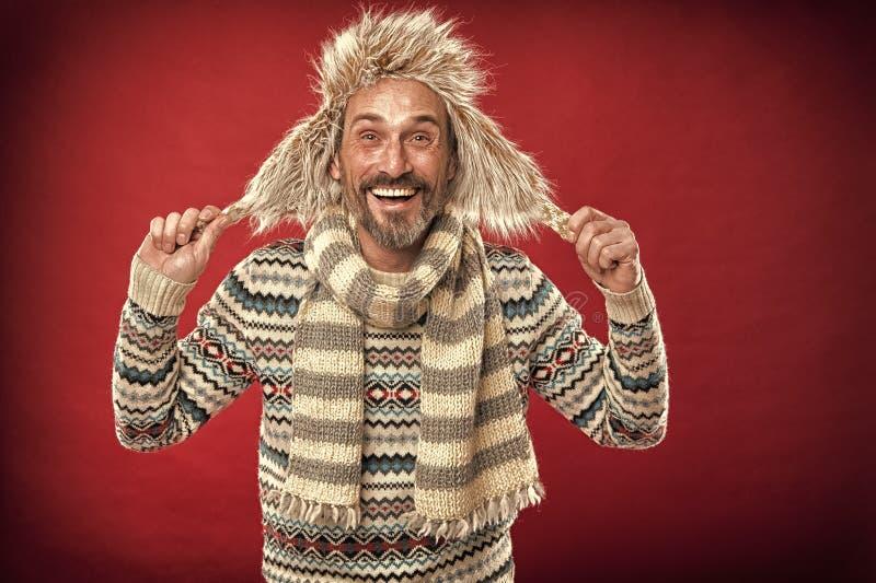 Warm blijven Bearded man die sweater met hoed en sjaal toegankelijk maakt Een winterensemble beschermt hem tegen kou Winter royalty-vrije stock afbeeldingen