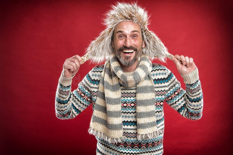 Warm blijven Bearded man die sweater met hoed en sjaal toegankelijk maakt Een winterensemble beschermt hem tegen kou Winter stock foto