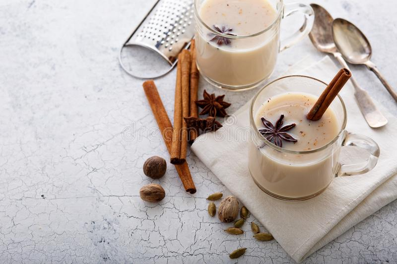 Warm chai tea with winter spices. Warm chai tea with milk and winter spices in glass mugs stock image
