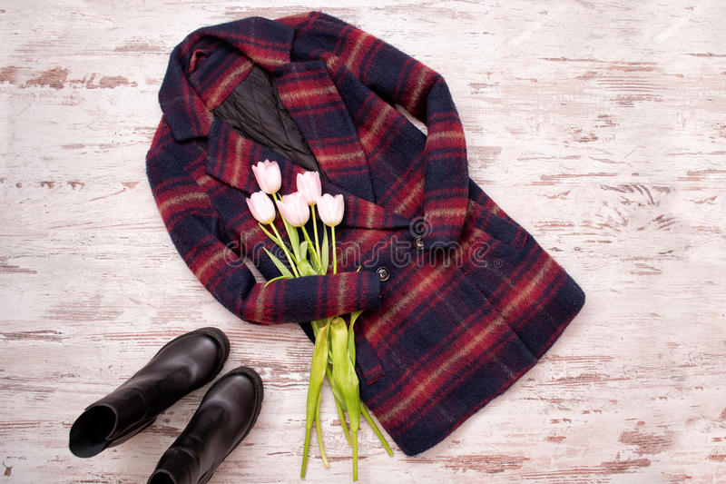 Warm checkered coats, black shoes, tulips. Fashionable concept, top view, wooden background stock photo