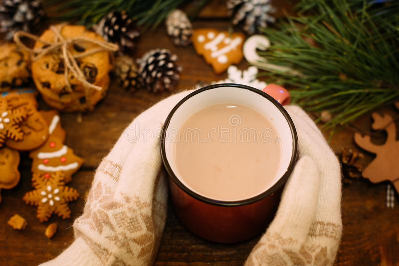 Warm Christmas holiday with latte and cookies. Top view unrecognizable woman with cup of drink in knitted gloves hands on festive background. Cozy xmas evening stock images