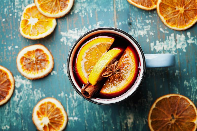 Warm christmas mulled wine or gluhwein with spices and orange slices on wooden teal table top view. Traditional drink on winter. royalty free stock photo