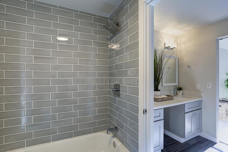 Warm and clean bathroom interior. Warm and clean bathroom boasts grey glass tile shower surround and double vanity cabinet with granite countertop royalty free stock photos