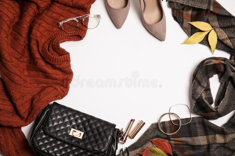 Warm clothes, autumn leaves and accessories on white background. Space for text. Warm clothes, autumn leaves and accessories on white background, top view. Space stock photography