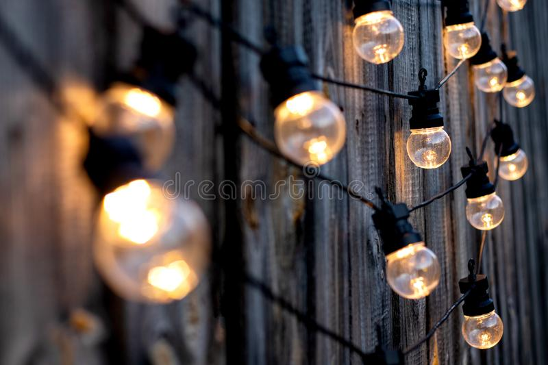 Warm color LED light bulbs on old wooden background in the garden, copyspace, outdoor lighting deciration concept royalty free stock photos