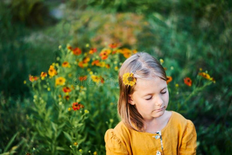 Warm colours flower little girl closed eyes dream sleep. Yellow orange green flowers autumn kid dream royalty free stock photography