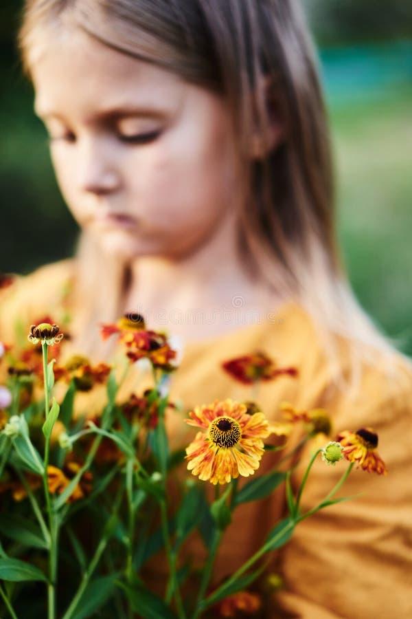 Warm colours flower little girl melancholic emotional. Yellow orange green flowers autumn vertical lifestyle stock photo