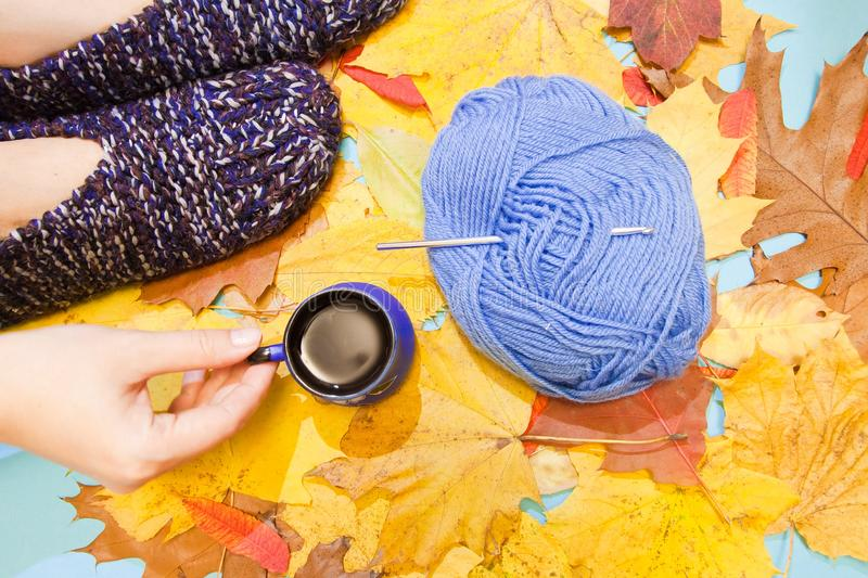 Warm comfortable knitted slippers, a hand holding a cup of hot coffee, and a ball of woolen or cotton yarn with crochet hook. Cool flat lay for creative people royalty free stock image