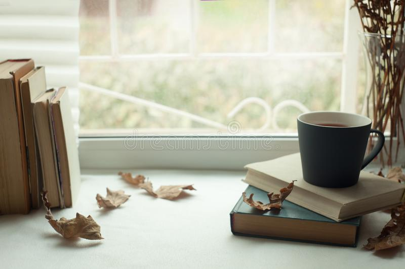Warm and comfy autumn concept. Book, cup of tea and candlestick on window sill in house. Reading and relaxing in cold weather. At home. Quiet silent homely royalty free stock photography