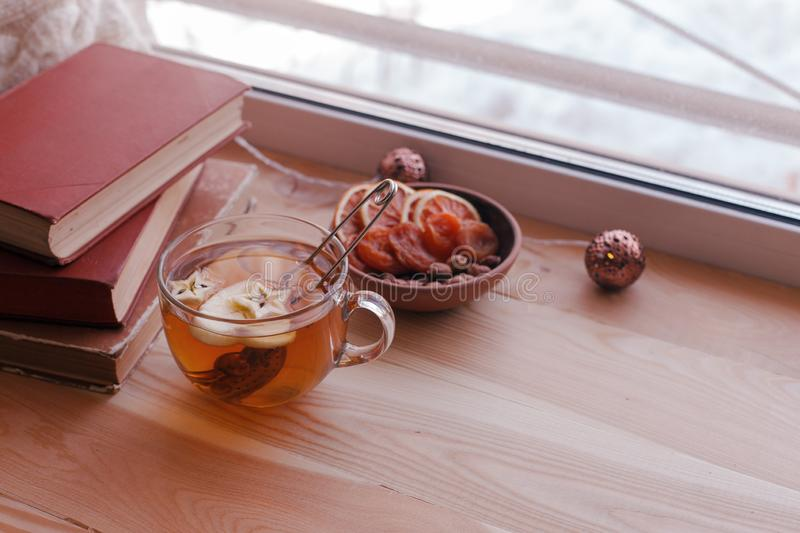 Warm and comfy autumn concept. Book, cup of tea on window sill in house. Reading and relaxing in cold weather at home. Quiet stock photography