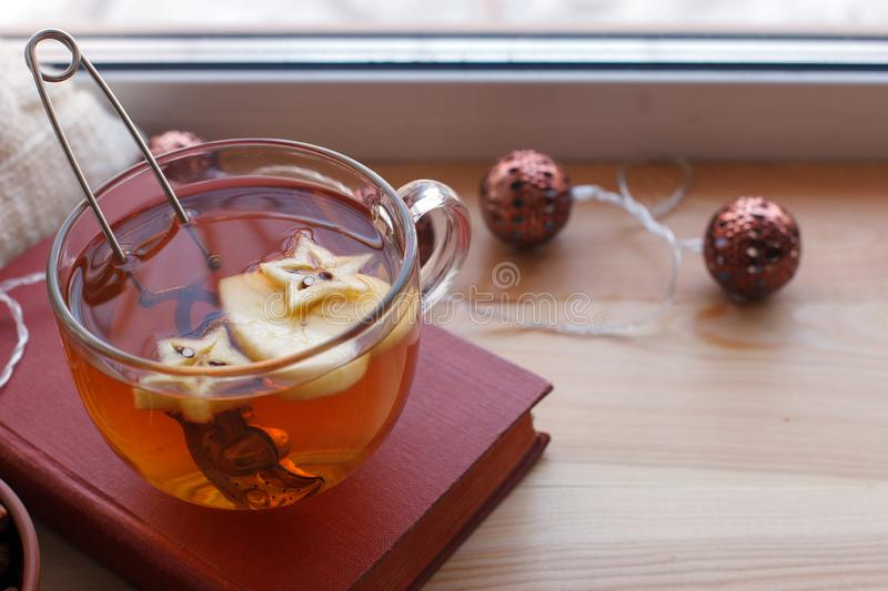 Warm and comfy autumn concept. Book, cup of tea on window sill in house. Reading and relaxing in cold weather at home. Quiet royalty free stock photography