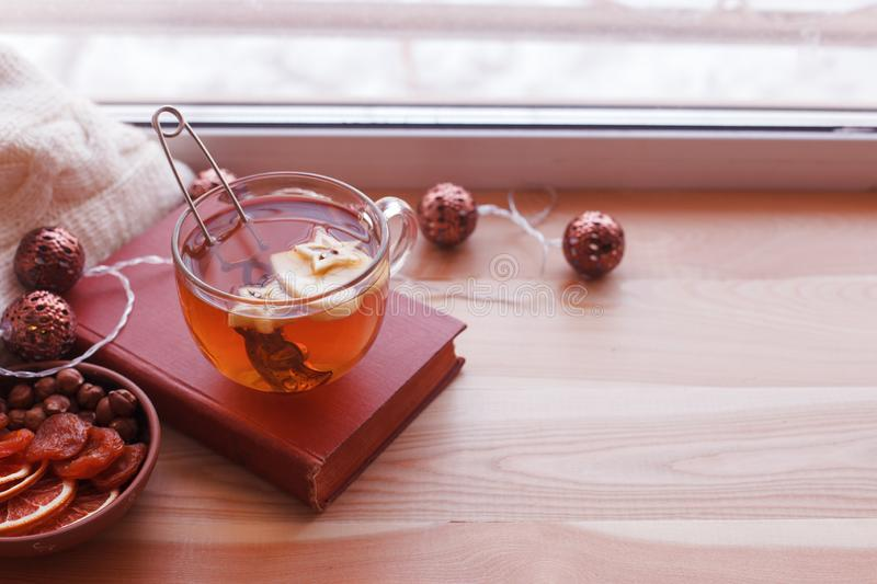 Warm and comfy autumn concept. Book, cup of tea on window sill in house. Reading and relaxing in cold weather at home. Quiet stock image