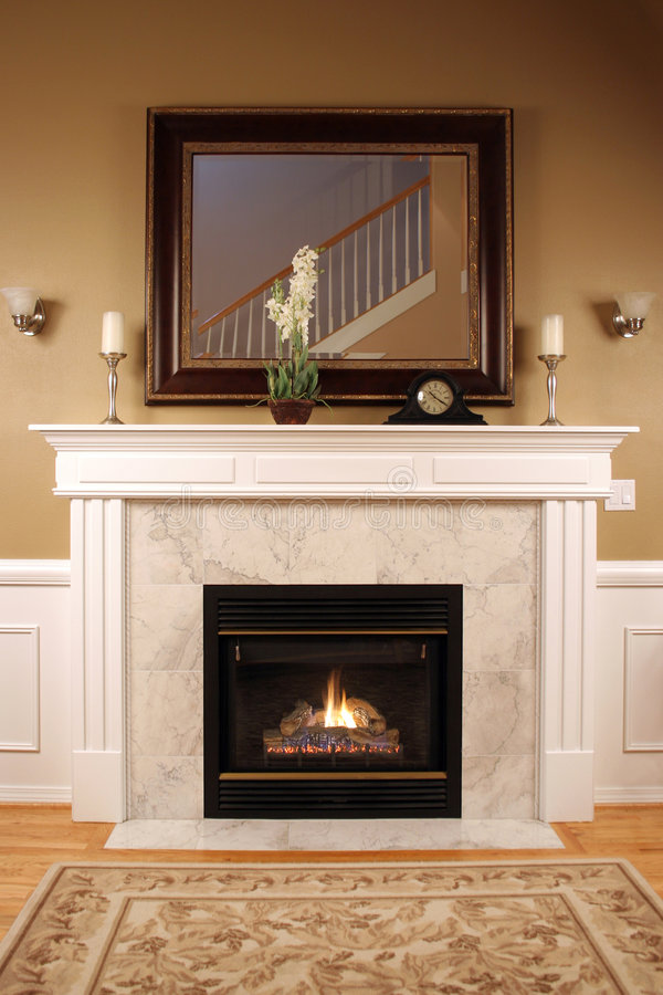 Warm and Cozy Fireplace. A lit fire with a beautiful mantle and mirror stock images
