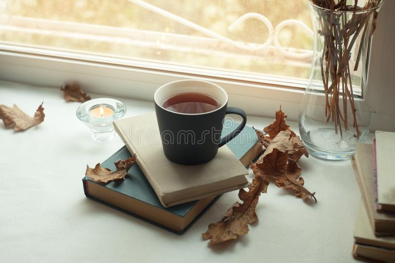 Warm and cozy scene with old book, cup of tea and candle on a table. Fall weekend, autumn lifestyle. royalty free stock photos