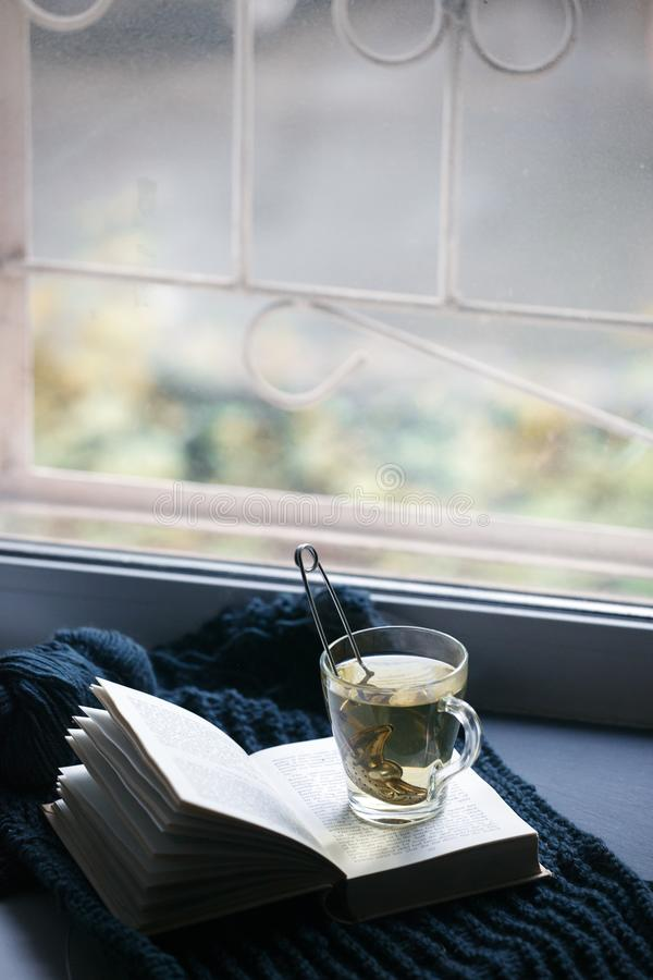 Warm and cozy window seat with warm plaid, cup of tea and book, rustic scandinavian minimal style home decor, unplud, relax,. Calmness autumn winter concept royalty free stock image