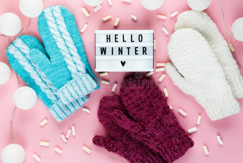 Warm, cozy winter clothing hat, mittens, lightbox and christmas decorations as frame on pastel pink background. Christmas concept flat lay. Hello winter title stock photos