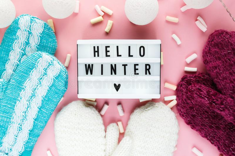 Warm, cozy winter clothing hat, mittens, lightbox and christmas decorations as frame on pastel pink background. Christmas concept flat lay. Hello winter title royalty free stock image