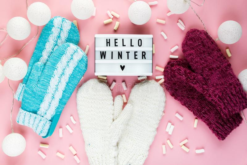 Warm, cozy winter clothing hat, mittens, lightbox and christmas decorations as frame on pastel pink background. Christmas concept flat lay. Hello winter title royalty free stock photography