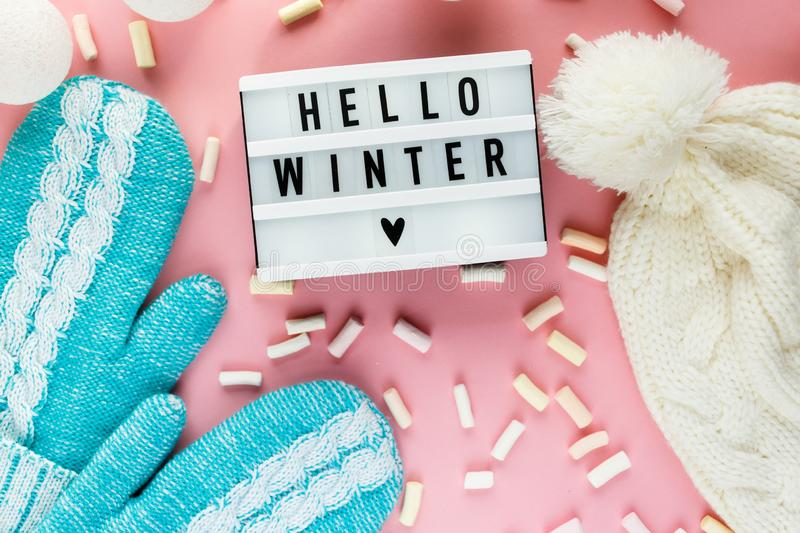 Warm, cozy winter clothing hat, mittens, lightbox and christmas decorations as frame on pastel pink background. Christmas concept flat lay. Hello winter title stock photography