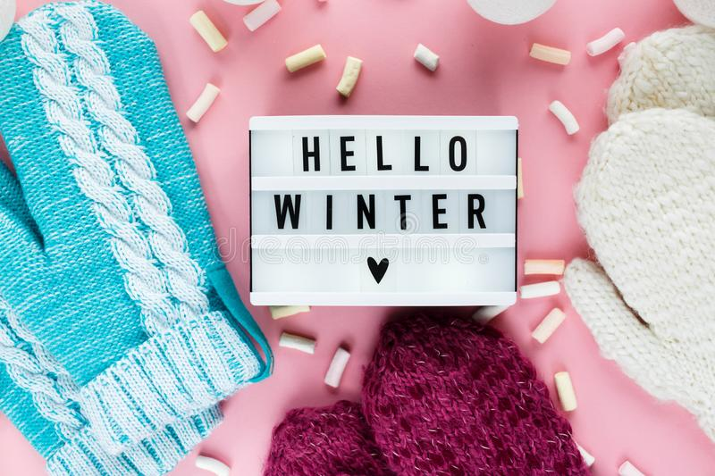 Warm, cozy winter clothing hat, mittens, lightbox and christmas decorations as frame on pastel pink background. Christmas concept flat lay. Hello winter title stock images