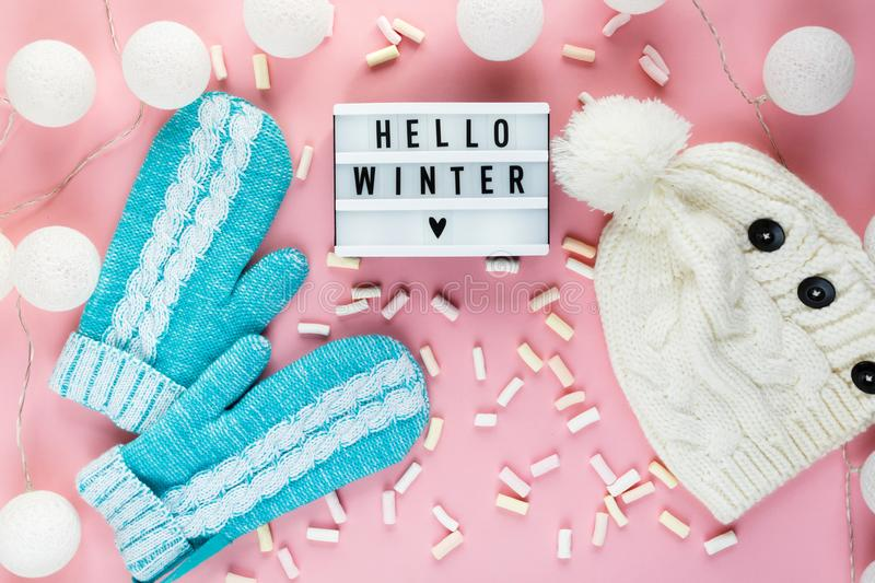 Warm, cozy winter clothing hat, mittens, lightbox and christmas decorations as frame on pastel pink background. Christmas concept flat lay. Hello winter title royalty free stock photo