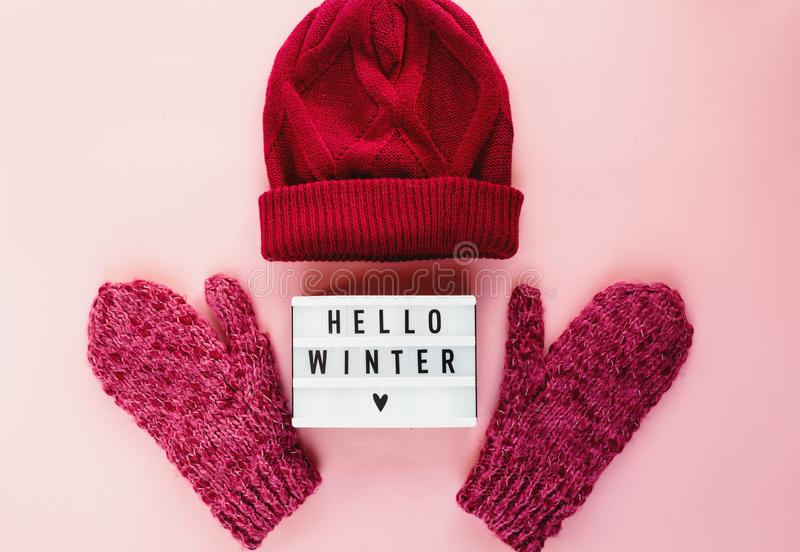 Warm, cozy winter mittens, lightbox on pastel on pink background. Christmas, New Year concept flat lay. Warm, cozy winter mittens, hat, lightbox on pastel on stock photo