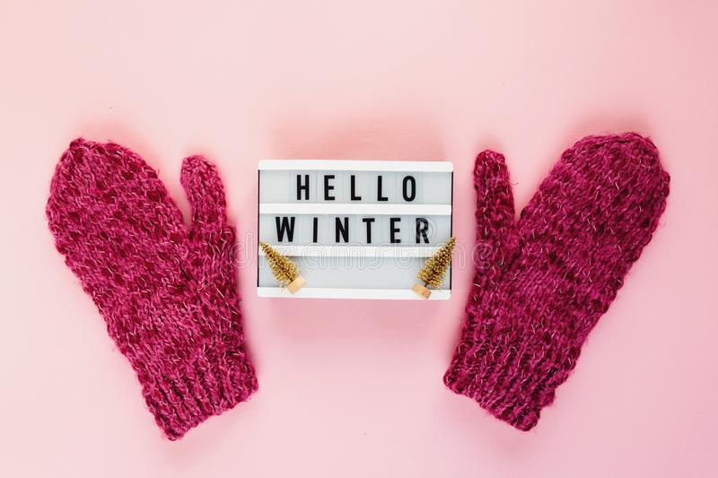 Warm, cozy winter mittens, lightbox on pastel on pink background. Christmas, New Year concept flat lay. Hello winter title royalty free stock image