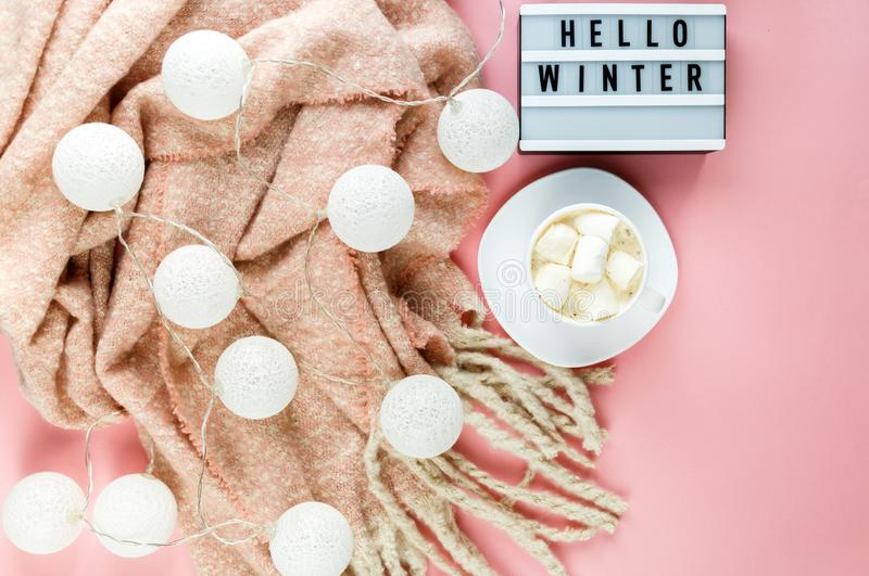 Warm, cozy winter scarf, lightbox on pastel and cup of coffee with marshmallow pink background. Christmas, New Year. Concept flat lay. hello winter title stock photos
