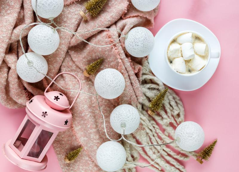 Warm, cozy winter scarf, lightbox on pastel and cup of coffee with marshmallow pink background. Christmas, New Year. Concept flat lay. hello winter title stock image
