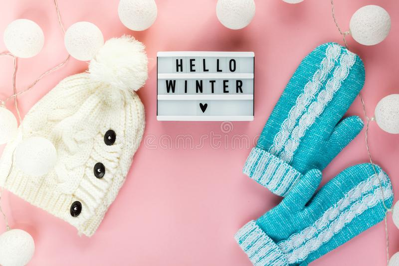Warm, cozy winter scarf, lightbox on pastel and cup of coffee with marshmallow pink background. Christmas, New Year concept. Warm, cozy winter scarf, mittens stock image