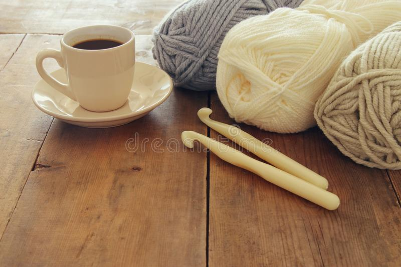 Warm and cozy yarn balls of wool and hot cup of coffee on wooden table.  royalty free stock photos