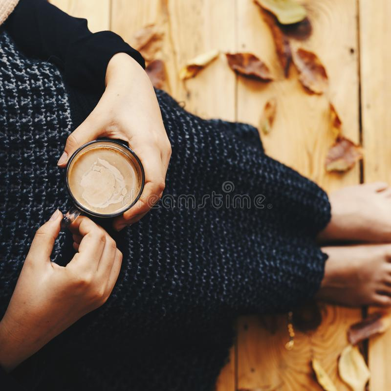 A warm cup of coffee in woman hands. Young female sitting on wooden floor with fall leaves. Girl covered with plaid and drinking royalty free stock photo