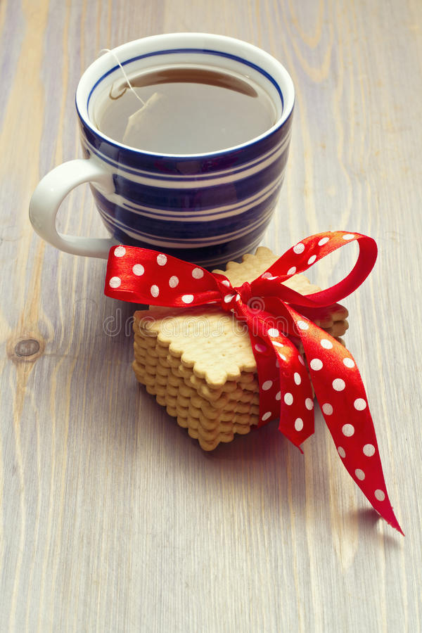 Warm cup of tea with cookies. On wooden tabletop royalty free stock photography
