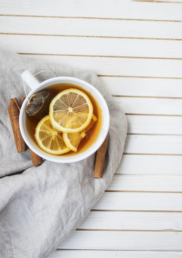 Warm cup of tea with lemons and cinnamon stock images