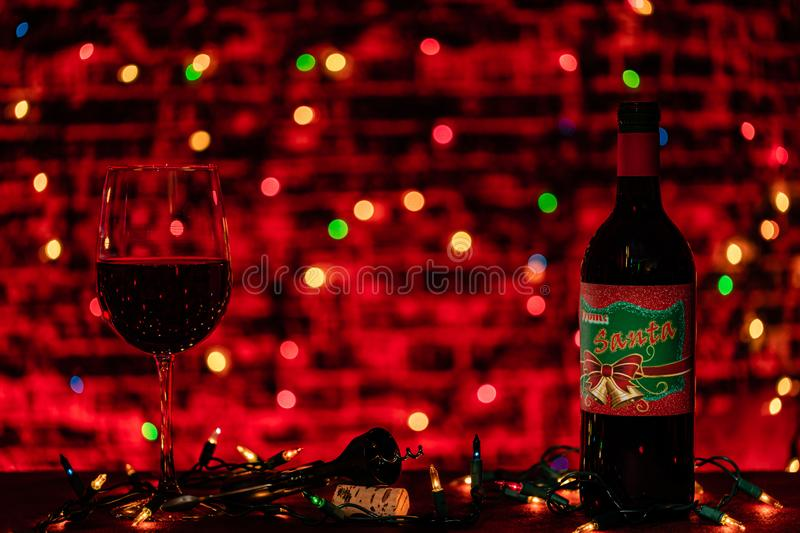A warm darkly lit scene of a glass and a bottle of wine ready for a holiday celebration. the only lighting is the Christmas lights stock photo