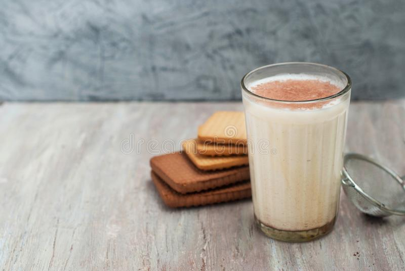 Warm Drink with Milk and cinnamon Powder on Silver Plate and Cocoa Biscuits on gray rustic Background. Horizontal image. Warm Drink with Milk and cinnamon royalty free stock images