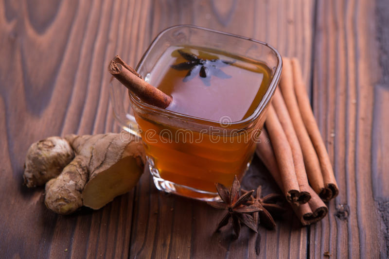 Warm drink for winter: tea, cinnamon, star anise, and ginger. On brown wooden background royalty free stock images