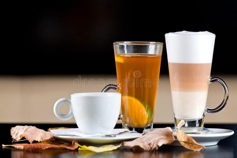Warm drinks: coffee, tea, latte with autumn leaves royalty free stock photos