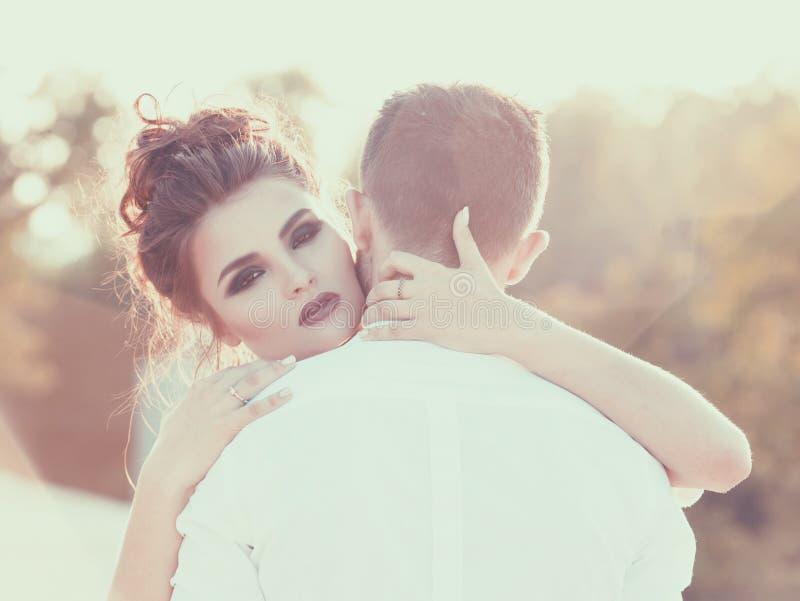 Warm embrace. Girl hugging her boyfriend. Vintage royalty free stock photos
