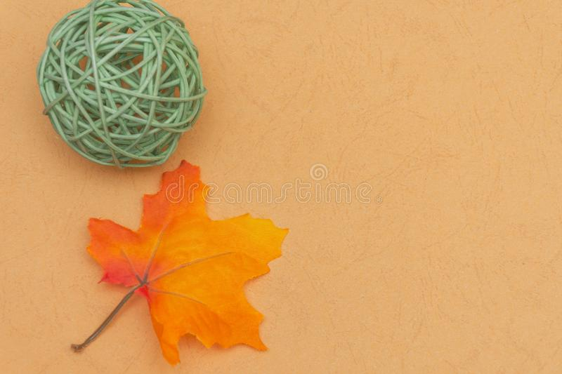 Warm fall seasonal orange  flatlay with festive green wicker reed ball and maple leaf on open concept and copy space availability. Warm fall seasonal orange stock photos