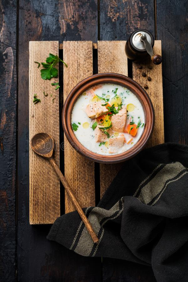 Warm Finnish creamy soup with salmon and vegetables in old ceramic bowl on old wooden background. Rustic style. Top view royalty free stock photos