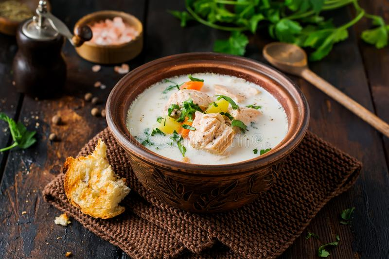Warm Finnish creamy soup with salmon and vegetables in old ceramic bowl on old wooden background. Rustic style stock photo