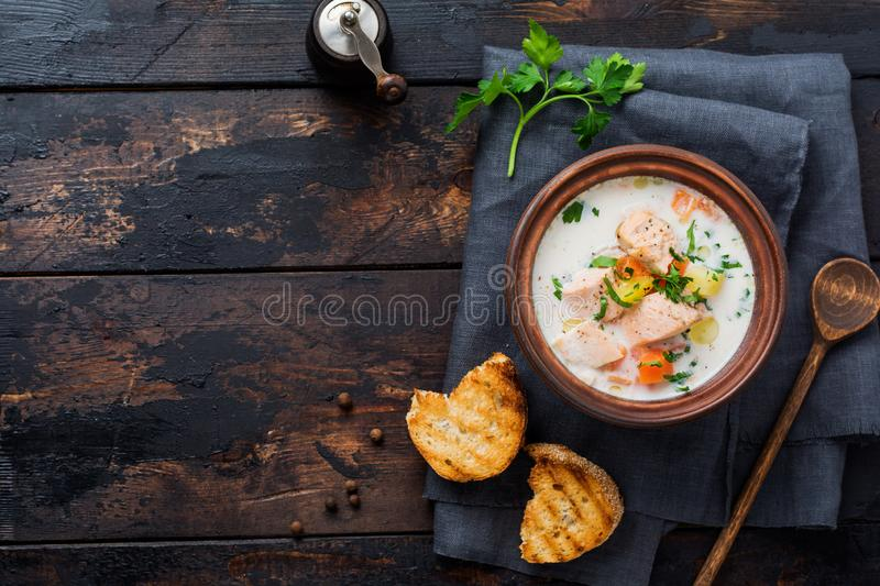 Warm Finnish creamy soup with salmon and vegetables in old ceramic bowl on old wooden background. Rustic style. Top view royalty free stock images