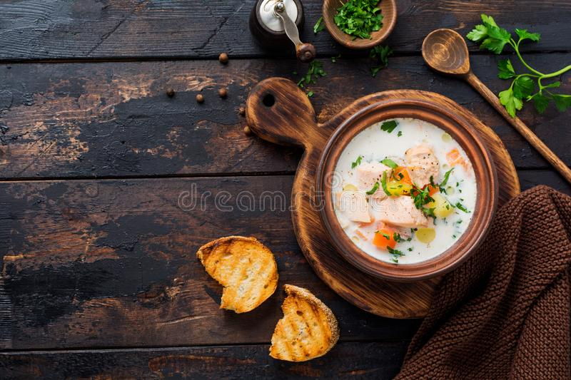 Warm Finnish creamy soup with salmon and vegetables in old ceramic bowl on old wooden background. Rustic style. Top view stock image
