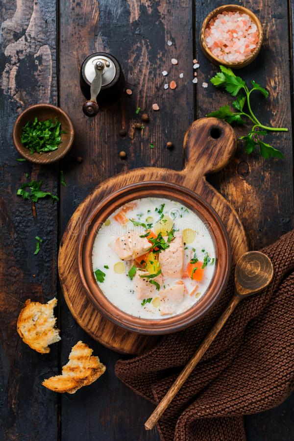 Warm Finnish creamy soup with salmon and vegetables in old ceramic bowl on old wooden background. Rustic style. Top view stock photo